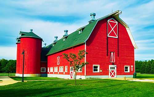 red barn with green roof and red silos